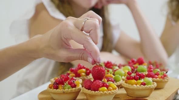 Thumbnail for In the Kitchen Concept. The Family Decorates the Pie and Muffins with a Berry.