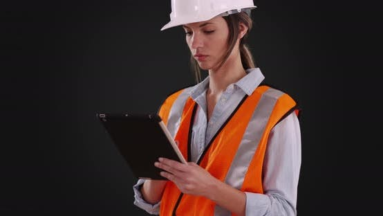 Thumbnail for Woman in orange vest and hardhat working on tablet on solid gray background