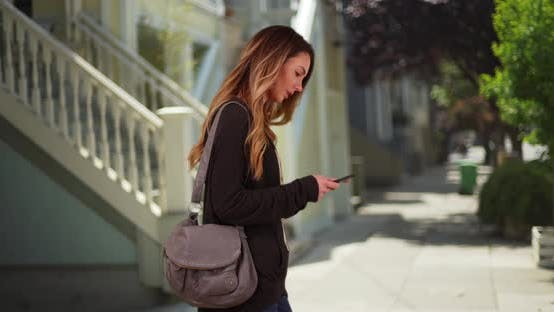 Thumbnail for White millennial girl messaging on cell phone outdoors on sidewalk during day