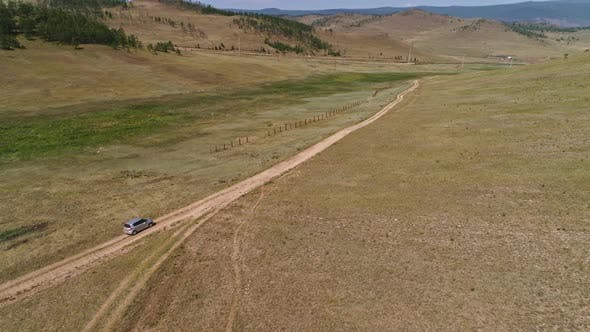 Thumbnail for Aerial Footage Filmed with Drone of Pickup Car Riding in Steppe. the Car Travels Along the Steppe To
