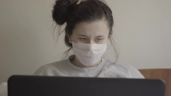 Close-up Portrait of Young Ill Woman in Face Mask Sneezing As Using Laptop