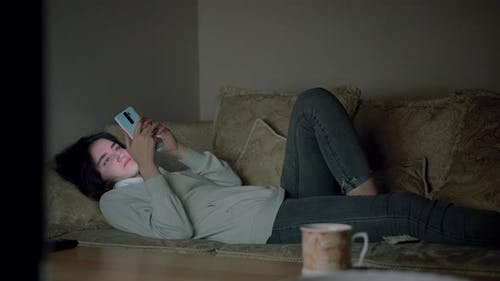 A Lonely Girl Spends the Evening Alone Lying on the Couch with a Mobile Phone