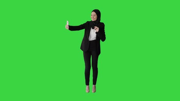Thumbnail for Smiling Arab Woman in Hijab Taking Selfie Pictures on Her Mobile Phone on a Green Screen, Chroma Key