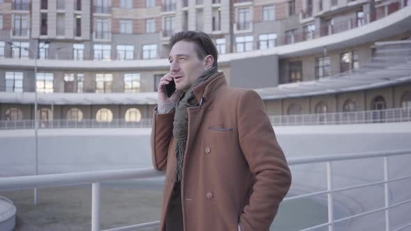 Cover Image for Portrait of Attractive Successful Man in Brown Coat Standing in the City Street Talking By Mobile