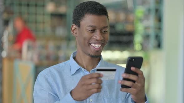 Young African Man Making Online Payment on Smartphone
