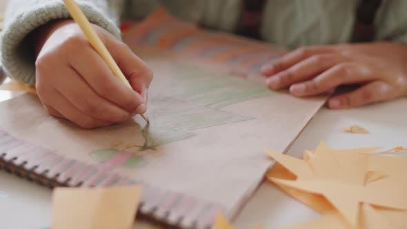 Girl Drawing Christmas Tree in Album