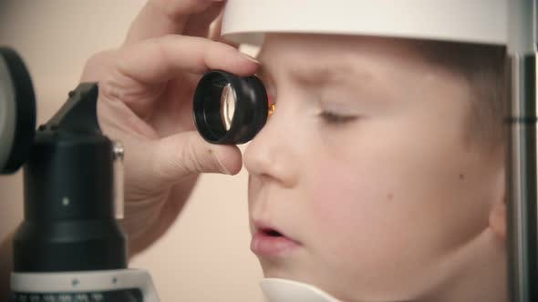 Thumbnail for A Little Boy Having a Treatment in Eye Clinic - Looking Through the Lens in the Device