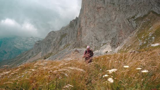 Thumbnail for Smiling Female Tourist Walking with Trekking Poles Among Tall Yellow Grass Under Large Mountain