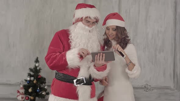 Thumbnail for Santa and Beautiful Young Smiling Woman Using Tablet