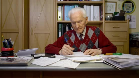 Cover Image for Senior Businessman Writing on Paper at Table in Office