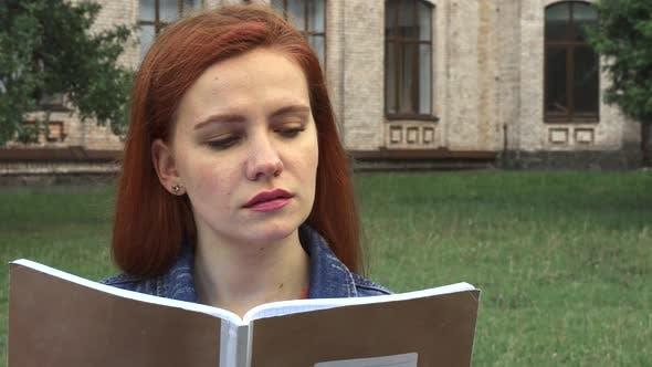 Girl Reading and Smiling at Camera