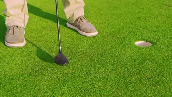 Man Play Golfing And Putting Ball In Hole. Close-up.