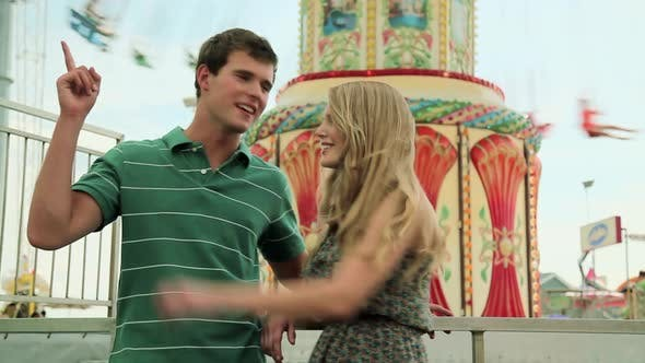 Thumbnail for Teenage couple at fun fair, girl dragging boyfriend away