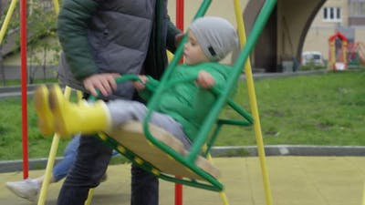 Boy Riding on Swing and Father Rocking Him