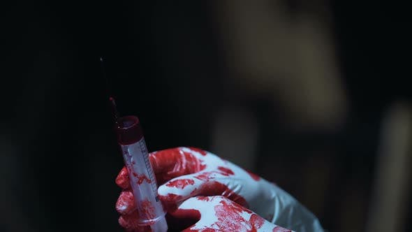 Thumbnail for Crazy Nurse Holding a Syringe With Blood in Hands Horror Scene Close Up