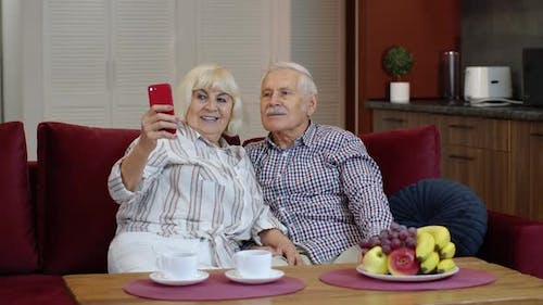 Senior Family Having Fun, Making Selfie Photos, Recording Video Together on Smartphone at Home