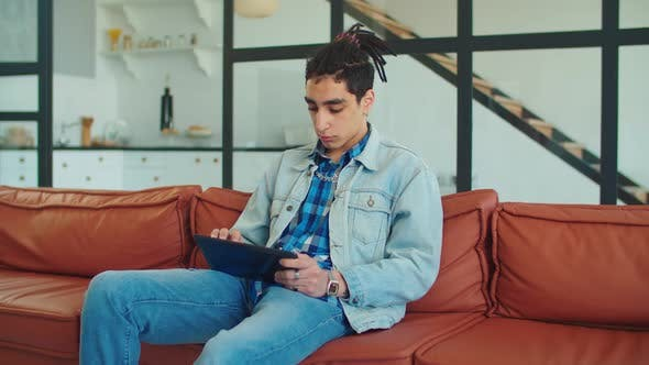 Thumbnail for Stylish Arabic Man with Tablet Pc Relaxing on Sofa