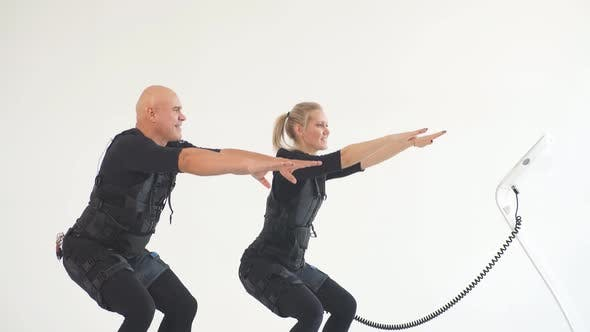 Thumbnail for Man and Woman in EMS Suits Developing Core Strength