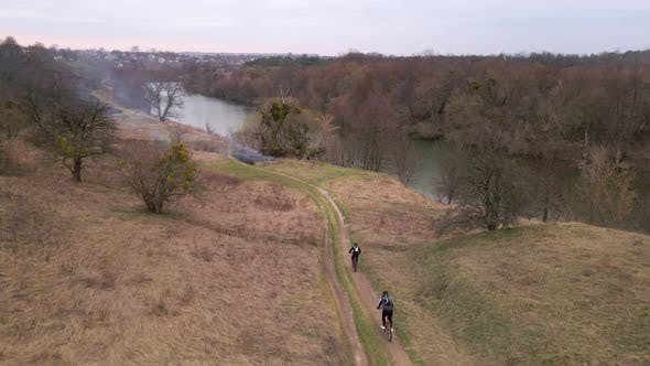 Slow Motion Aerial Shot of Young Sport Men Ride Bicycles on Forest Road at Spring Cloudy Evening