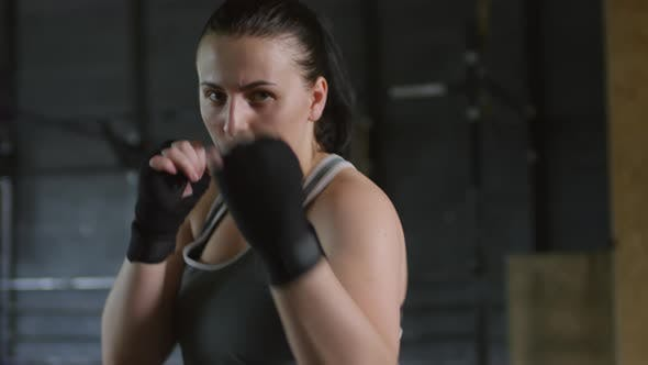 Female Fighter with Wrapped Hands Punching at Camera in Gym