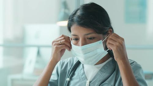 Portrait of Hispanic Female Doctor Putting on Protective Mask