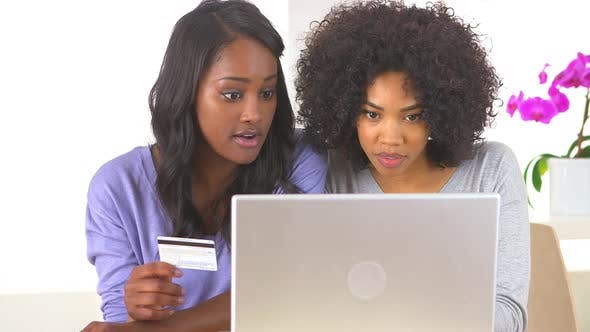 Thumbnail for Two African American friends making online purchase with laptop