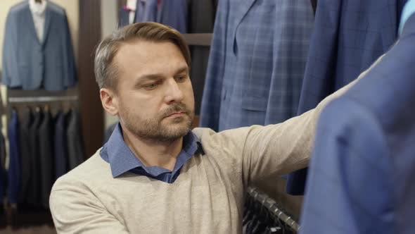 Thumbnail for Man Choosing Suit in Menswear Store