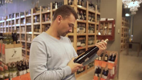 Thumbnail for Handsome Man Learning the Label on the Wine Bottle in a Wine Shop