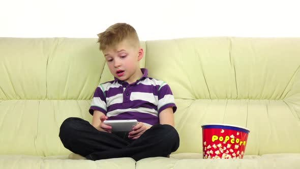 Thumbnail for Boy Plays on Phone Online Game, Eats Popcorn. Slow Motion