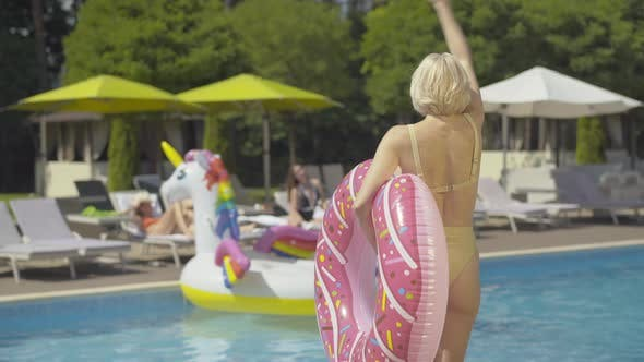 Back View of Confident Blond Woman with Donut Swimming Ring Coming To Pool and Waving To Blurred