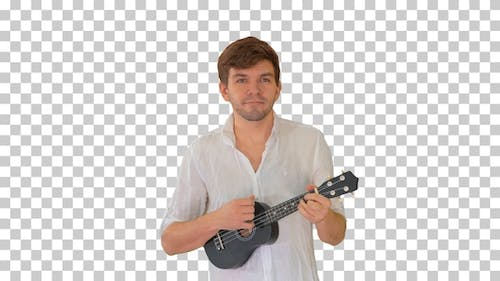 Young man playing ukulele while walking, Alpha Channel