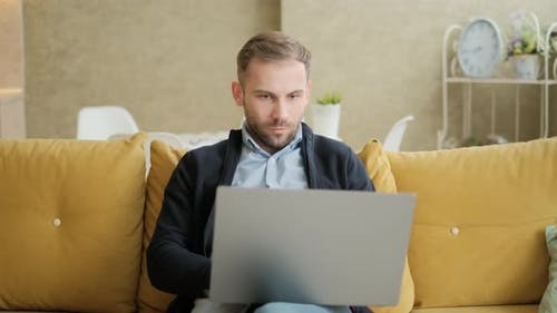Remote Job. A Man Is Working with Documents on Laptop Remotely at Home. A Business Man