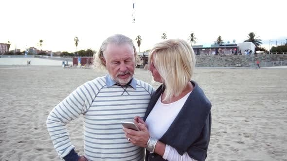 Thumbnail for Happy Senior Man and Woman Couple Sitting Together at a Table By a Beach Talking on a Cell Phone