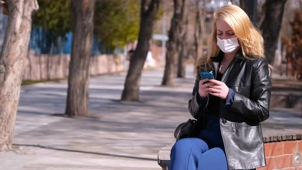 Young Girl in Mask With Smartphone