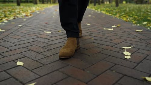 Low View of Unrecognizable Man in Boots and Dark Trousers