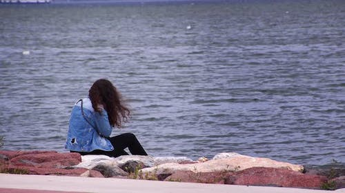 Curly Haired Young Girl Sits On Stones By The Sea