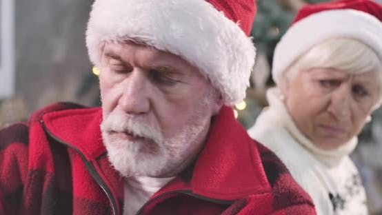 Thumbnail for Close-up Face of Sad Old Caucasian Man with White Beard Wearing Red Christmas Hat Looking Away