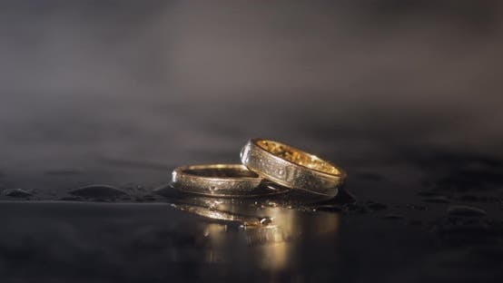 Thumbnail for Wedding Rings on Dark Water Surface Shining with Light