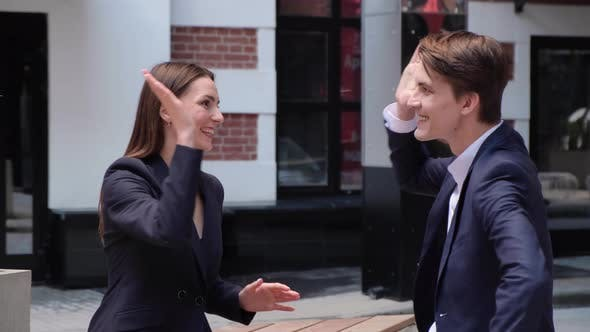 a young couple sit on a bench and chat, high-five each other
