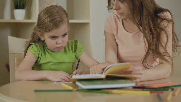 Thumbnail for Bouleversé petite fille faire des tâches scolaires avec la mère, ennuyé ou fatigué des devoirs