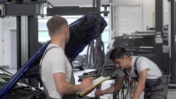 Thumbnail for Two Mechanics Discuss Repairing Broken Automobile at the Garage
