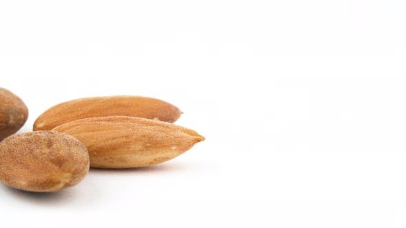 Thumbnail for Half Frame of Star Shaped Six Peeled Almonds Rotating the in the Left Side on the White Background