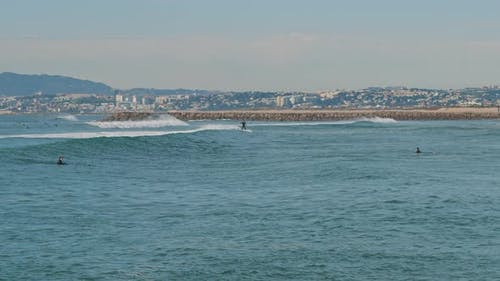 People catching waves in the ocean near the Lisbon coast, Portugal.