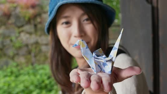 Thumbnail for Woman hold a paper crane origami in Japanese house