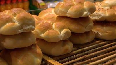 A Baker Puts Bread Rolls on a Shelf in a Bakery - Closeup