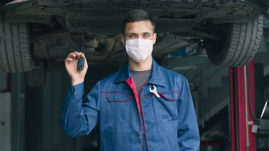Thumbnail for Young Mechanic in Protective Mask Showing Keys After Settling Car, Vehicle Ready To Start