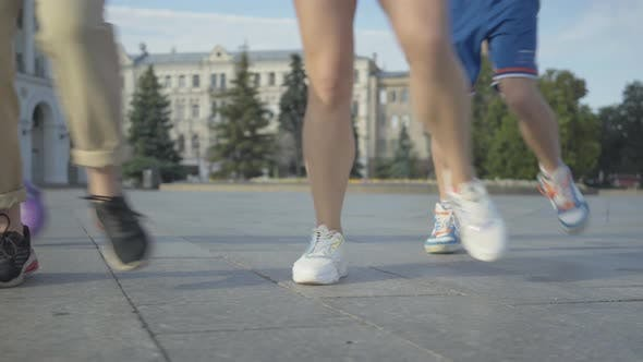 Legs of Four Unrecognizable Men and Women Dancing Modern Dance Outdoors. Group of Joyful Young