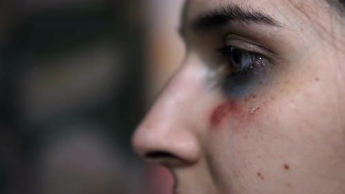 Nahaufnahme einer Träne auf dem Gesicht einer jungen Frau mit einem Trauma von Gewalt