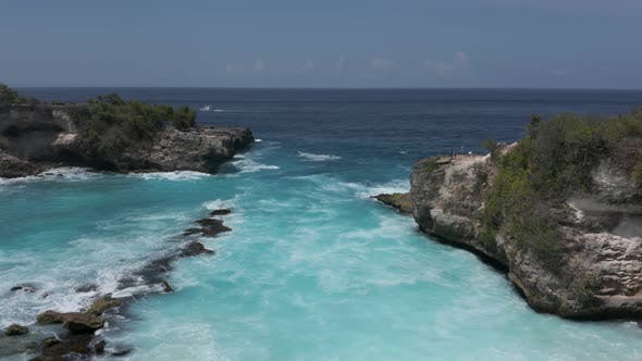 Thumbnail for Aerial drone view of ocean waves breaking in a small rocky bay in Indonesia