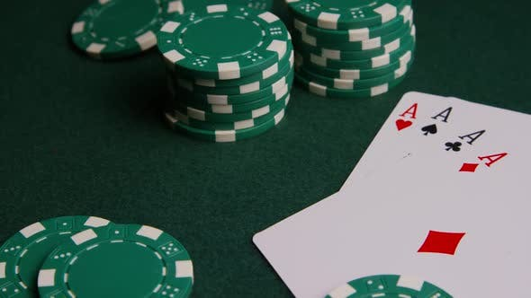Rotating shot of poker cards and poker chips on a green felt surface - POKER 005
